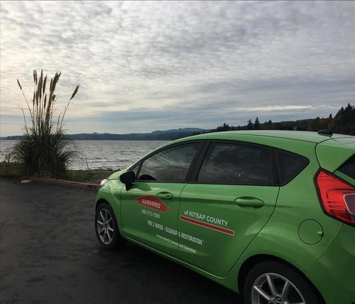Small Green SERVPRO vehicle overlooking a body of water, phone number prevalent