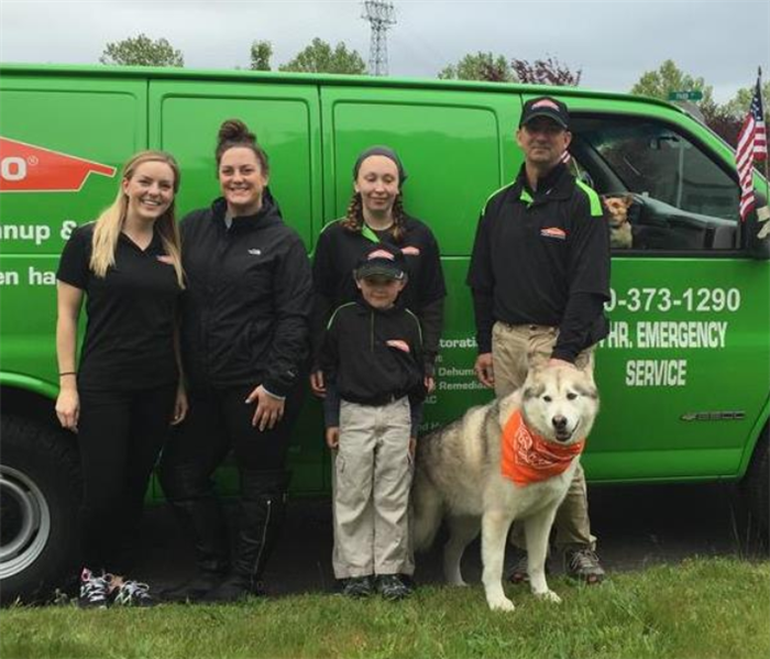 People and dog standing in front of SERVPRO van.